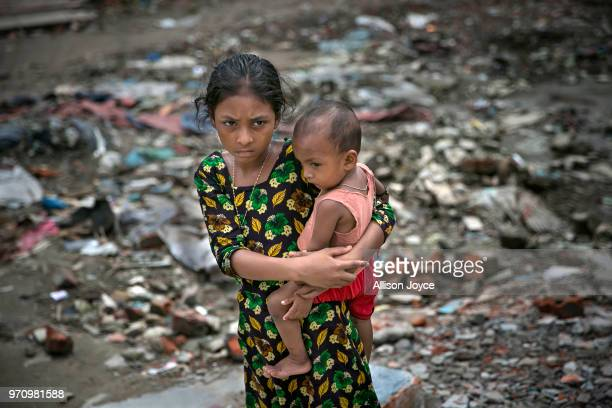 A girl holds a baby next to a polluted canal that leads to the Buriganga river in Shyampur June 10 2018 in Dhaka Bangladesh Bangladesh has been...