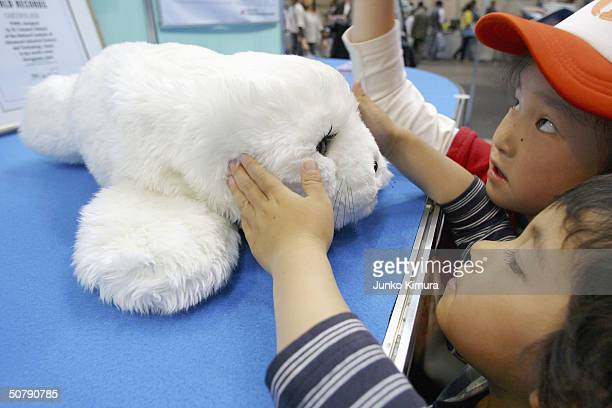 A girl holds a baby seal robot during the Robocup Japan Open 2004 at held at Intex Festa 2004 on May 1 2004 in Osaka Japan The Robocup Japan Open...