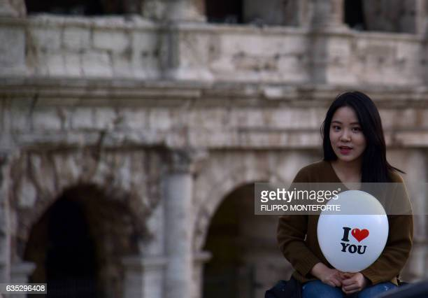 Girl holds a ballon with the lettering 'I love you' in front of the Colosseum in Rome on Valentine's Day on February 14, 2017. / AFP / FILIPPO...