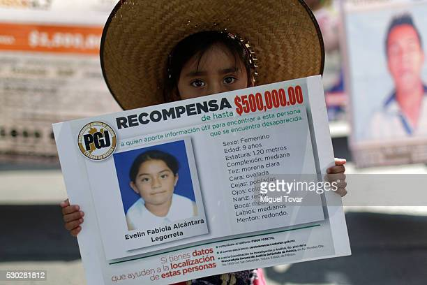 A girl holds a banner of her disappeared sister during a march on Mother's Day on May 08 2016 in Mexico City Mexico Mothers and other relatives of...
