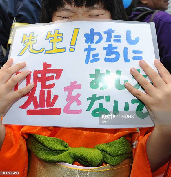 A girl holds a banner saying 'Teacher Please do not teach us the lie' during an antiChina protest rally in central Tokyo on November 6 2010 Japanese...