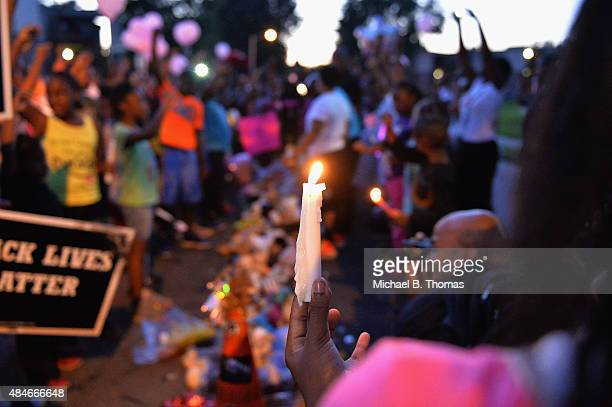 Girl holds a candle as children gather at the Michael Brown Jr. Memorial on Canfield Drive during a candlelight vigil held in honor of Jamyla Bolden...