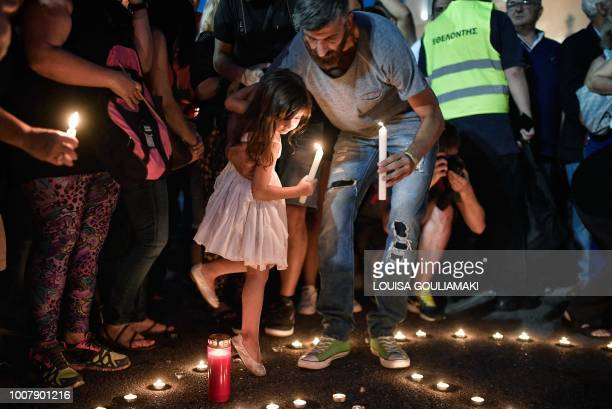 A girl holds a candle during a candlelight vigil in front of the Greek parliament in Athens on July 30 to commemorate victims of the country's worst...