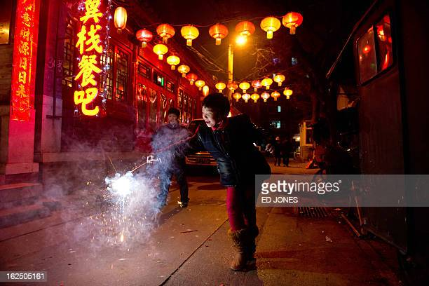 A girl holds a firecracker in an alleyway in Beijing during the lantern festival which marks the end of celebrations for the Chinese new year period...