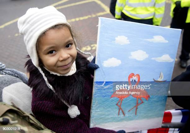 A girl holds a painting as Prince Harry and his fiance Meghan Markle arrive to Pop Brixton to see the broadcaster's work supporting young people...