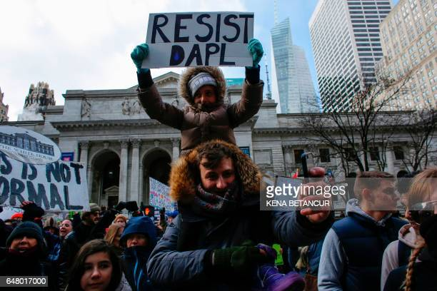 A girl holds a placard as she takes part of a protest against the planned Dakota Access Pipeline in North Dakota on March 04 2017 in New York / AFP...