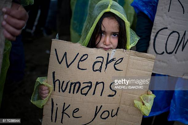 A girl holds a placard during a protest held by migrants and refugees to call for the reopening of the borders at a makeshift camp at the...