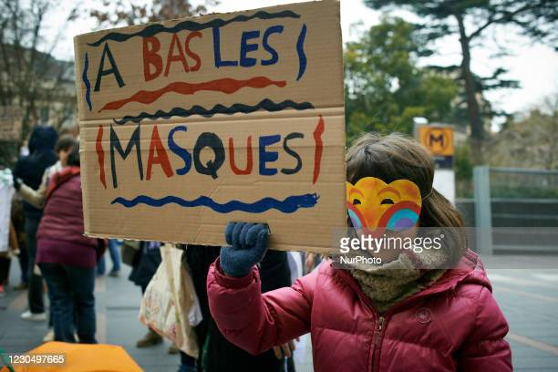 Girl holds a placard reading 'Drop the mask'. Parents and children gathered against the sanitary measures in school which makes protective face mask...