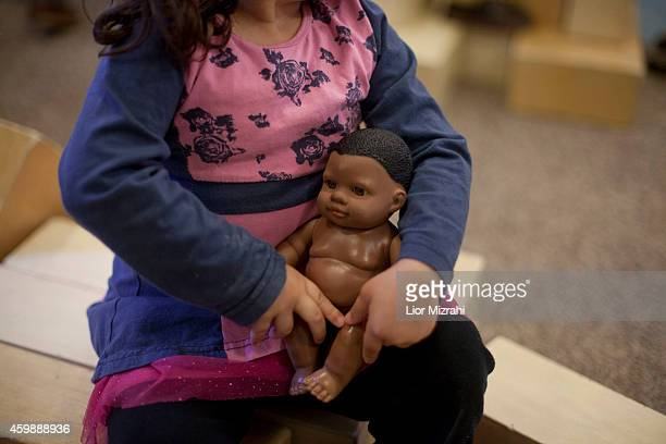 A girl holds a play doll at the YMCA kindergarten on December 3 2014 in Jerusalem Israel In the Jerusalem International YMCA Kindergarten the...