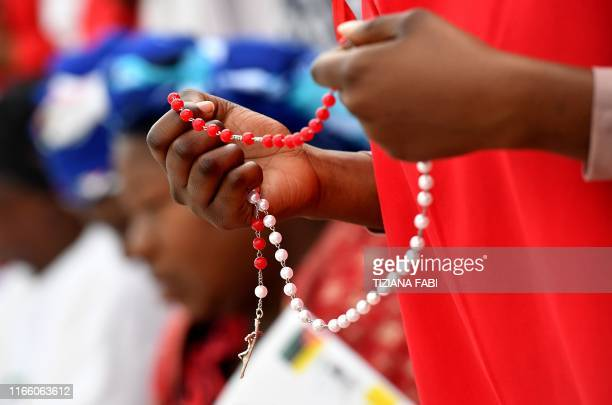 A girl holds a rosary prior the arrival of Pope Francis at the Cathedral of the Immaculate Conception in Maputo on September 5 2019 Pope Francis will...