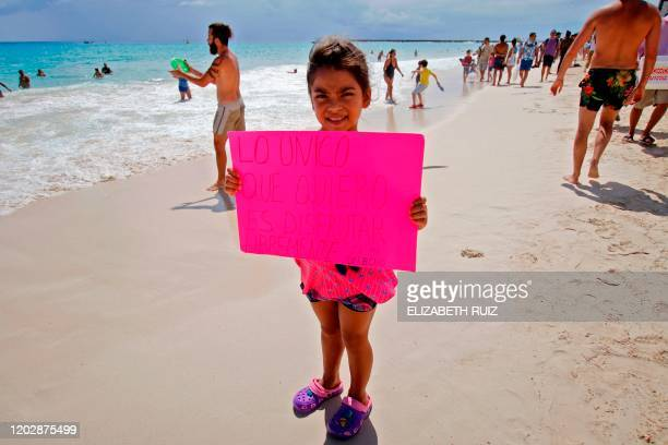 A girl holds a sign reading All I want is to enjoy freely It is my rigtht during a picnic as part of a protest in Playa del Carmen Mexico on February...