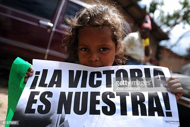 A girl holds a sign reading Victory is ours during a protest at El Pedregal neighborhood in Tegucigalpa Honduras on October 3 2009 Members of the...