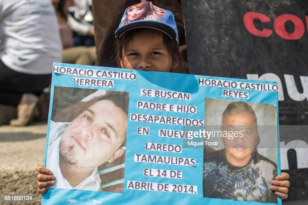 A girl holds a sign with images of his missing relatives during a march on Mother's Day on May 10 2017 in Mexico City Mexico Mothers whose children...