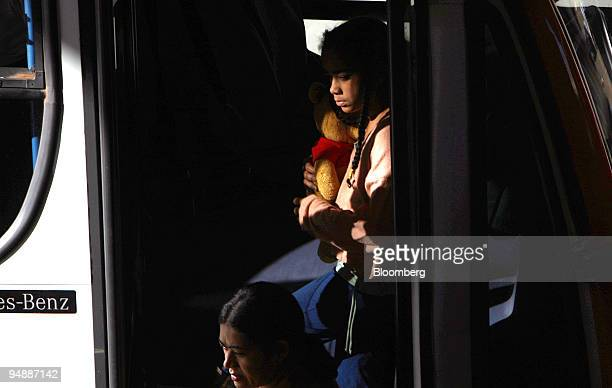 A girl holds a stuffed animal inside a public transportation bus at the central bus terminal in Brasilia Brazil on Friday June 6 2008 Built on open...