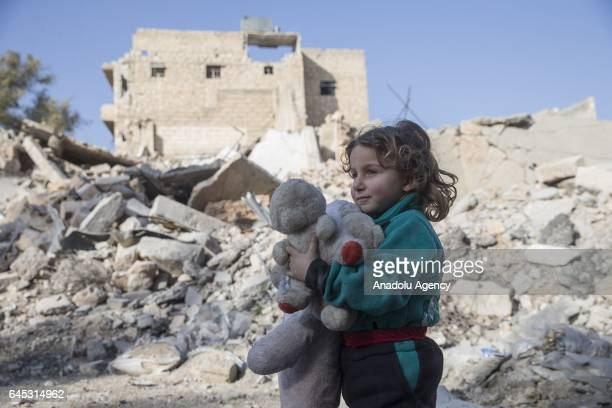A girl holds a teddy bear in the Syrian town of Al Bab after the town center has been entirely freed from Daesh terrorists by Free Syrian Army backed...