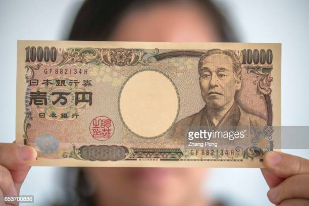 A girl holds a tenthousand Yen bank note in hand In the early march Japan's core inflation has returned for the first time in more than one year and...