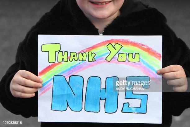 "Girl holds a thank you sign as she attends a national ""clap for carers"" to show thanks for the work of Britain's National Health Service workers and..."