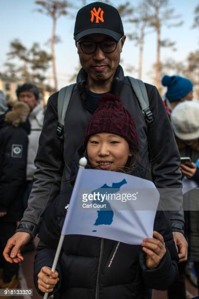 A girl holds a unified Korean flag as she queues to watch the Women's Ice Hockey Preliminary Round Group B game between Korea and Japan on day five...