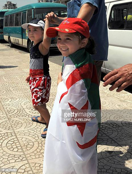 A girl holds an Algerian flag on her shoulders after it was given to her by scout children during a national independence rally on July 3 2008 in...