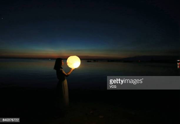 A girl holds an illuminated lantern on Poyang Lake during Qixi Festival on August 28 2017 in Jiujiang Jiangxi Province of China The performer draws a...