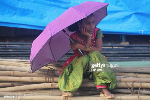 A girl holds an umbrella as she sits over bamboo poles in Mumbai India on 20 June 2019 According to a government agency Monsoon this year has been...
