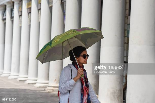 A girl holds an umbrella to protect herself from the scorching sun on a hot summer day at Connaught Place on June 7 2018 in New Delhi India Mercury...