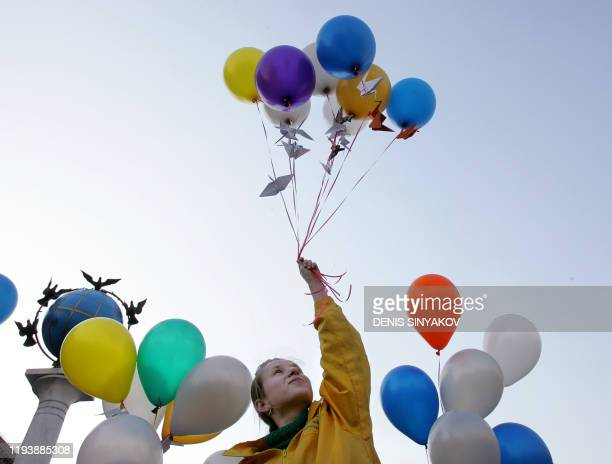 A girl holds balloons with origami Japanese folded paper cranes before releasing them in central Kiev as part of Chernobyl 20th anniversary...