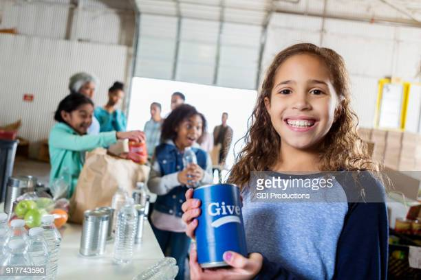 Girl holds collection can during food drive