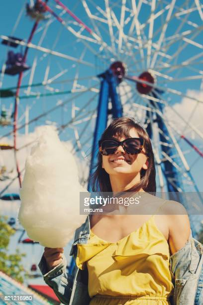Girl holds cotton candy in amusement park.
