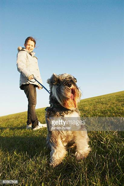 Girl holds dog on lead on hill