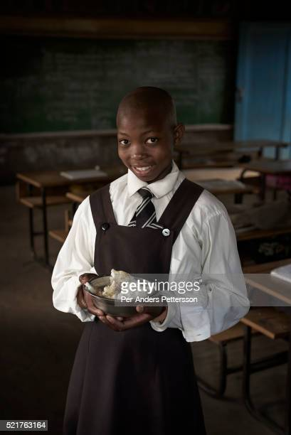 Girl holds her lunch box in a classroom at Masapong primary school on September 1 in Masapong district outside Maseru, Lesotho. The are given two...