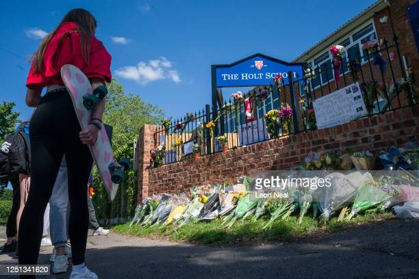 A girl holds her skateboard as students lay flowers and pay their respects to the murdered school teacher James Furlong outside The Holt School on...