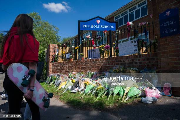 A girl holds her skateboard as students lays flowers and pay their respects to the murdered school teacher James Furlong outside The Holt School on...