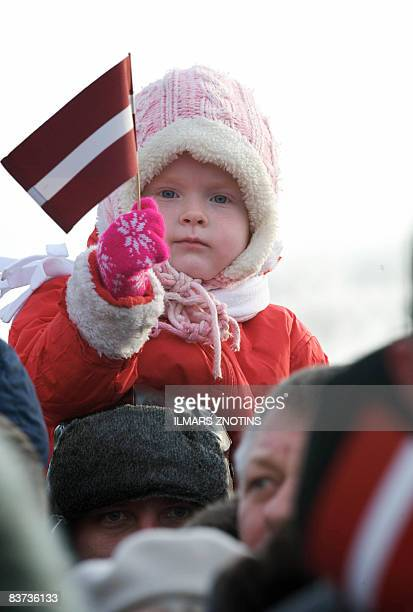 A girl holds holds a Latvian flag during a military parade on November 18 2008 to celebrate Latvia's 90th anniversary of independence from Russia an...