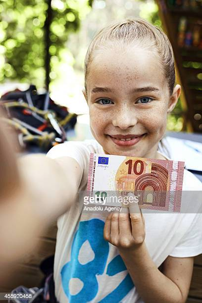 A girl holds new 10 euro banknote during a press conference in Frankfurt Germany on June 10 2014 The new banknote with new security features and its...
