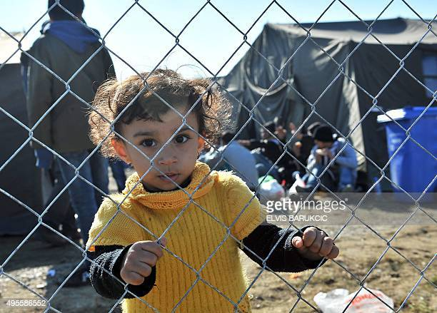 A girl holds on to a fence at a transit camp housing migrants and refugees in Slavonski Brod on November 4 2015 Thousands of newly arrived migrants...