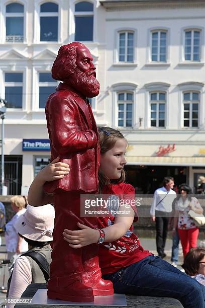 A girl holds one of the 500 one meter tall statues of German political thinker Karl Marx on display on May 5 2013 in Trier Germany The statues...