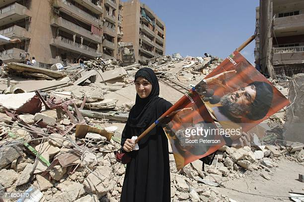 Girl holds posters of Hizbullah leader Sayyed Hassan Nasrallah, as Lebanese battered by five weeks of war between Israel and Hezbollah return to...