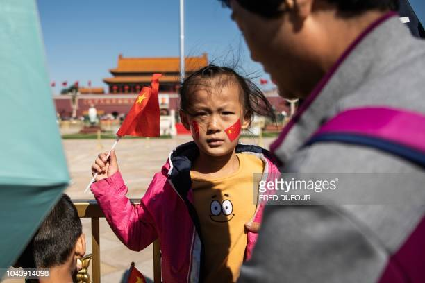 A girl holds the China national flag as she visits Tiananmen Square during National Day in Beijing on October 1 2018
