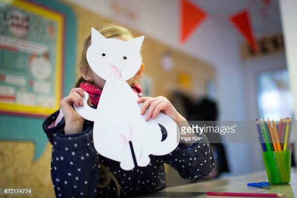 A girl holds up a cardboard cat in a social PopupStore on April 20 2017 in Berlin Germany on April 20 2017 in Berlin Germany Founder of this project...