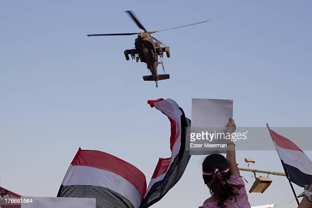 Girl holds up a sign as an army Apache helicopter flies low over Tahrir square on the 26th of July, the day army general Abdel Fattah el-Sisi called...