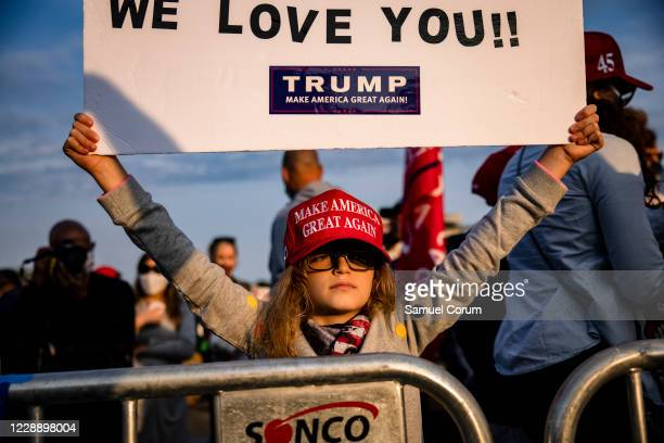 A girl holds up a sign wishing President Donald Trump good health outside of Walter Reed National Military Medical Center after the President was...