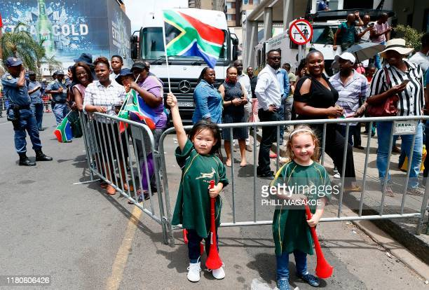 A girl holds up a South African flag as Springboks supporters cheer as the South African Rugby team parade through the central business district of...