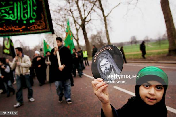 A girl holds up an image of Imam Hussein during the Ashura festival procession through Hyde Park on January 30 2007 in London The ten day event...