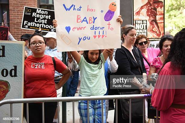 Girl holds up handlettered sign in front of Planned Parenthood A coalition of antiabortion protesters protested on Mott Street in Manhattan in front...