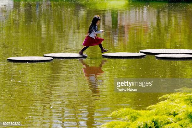 A girl hops over a step in a pond at the Keukenhof the world's largest flower and tulip garden park on May 10 2017 in Lisse Netherlands One of the...
