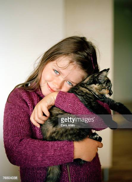 A girl hugging a cat.