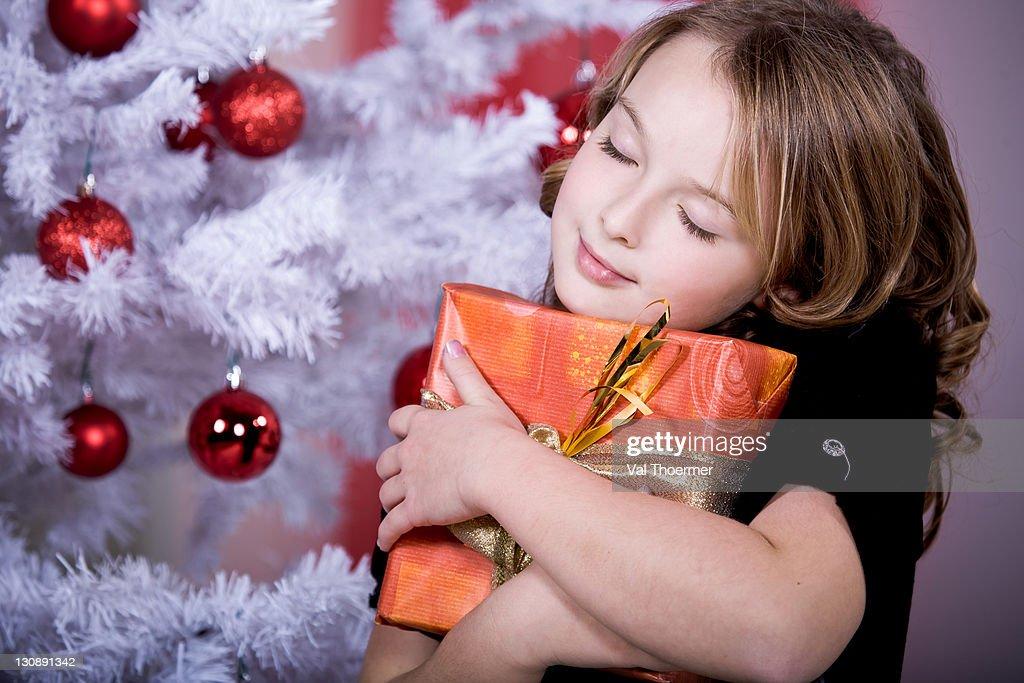 Girl hugging a Christmas present : Stock Photo
