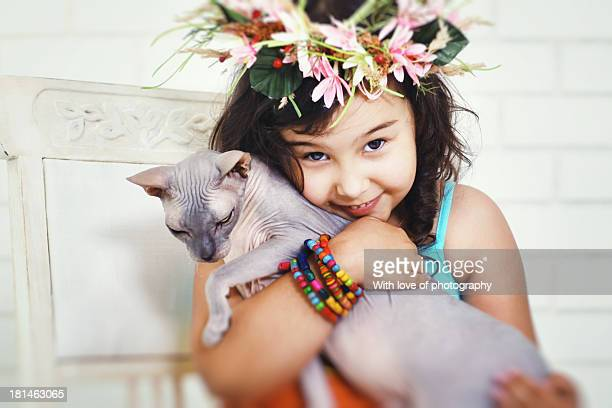 A girl hugging a sphynx cat in studio