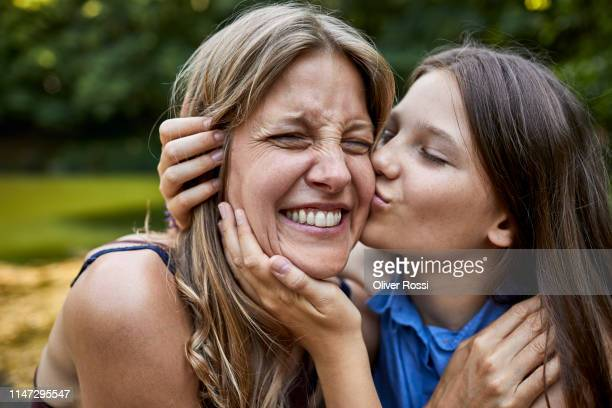 girl hugging and kissing happy mother - ungestellt stock-fotos und bilder
